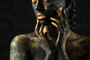 Foto op Aluminium Body Paint Beautiful woman with black and golden paint on her body against dark background, closeup