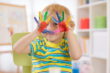 cute cheerful kid with hands painted in bright colors
