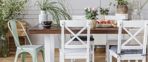 Panorama of chairs at wooden table with flowers in rustic dining room interior with plants. Real photo