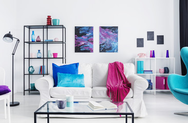 Pink blanket and blue cushions on white sofa in loft interior with table, lamp and posters. Real photo