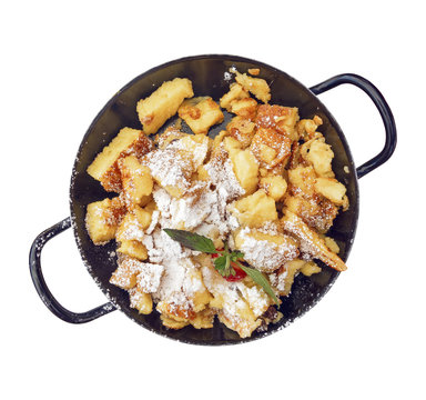 Kaiserschmarrn sugared in black iron pan isolated on white
