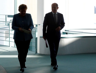 German Chancellor Angela Merkel and Finance Minister Olaf Scholz walk to a cabinet meeting at the Chancellery in Berlin