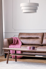 Lamp above wooden table in white living room interior with pink blanket on leather couch. Real photo