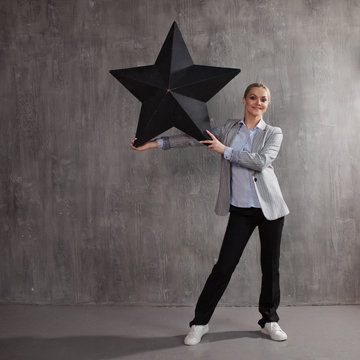 Be a star. A young woman in a business suit with a big black star in hand