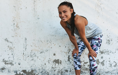 Young smilng woman during a break outdoors against concrete wall. Happy athletic female relaxing after exercises, looking at the camera, resting after workout outside. Wall mural
