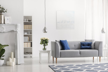 Grey settee with blue cushions in white elegant living room interior with flowers and painting. Real photo
