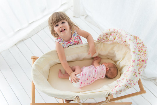 Smiling girl and newborn baby in cradle