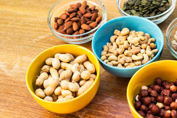 Assortment of mixed nuts on wood table background