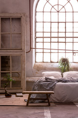Real photo of a wabi sabi bedroom interior with a big, old window and bed