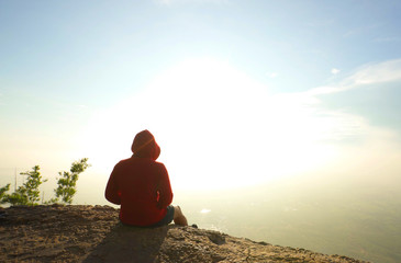 man in red hoodie sitting on mountain top viewpoint at sunrise