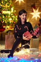 Beautiful happy young woman with christmas lights