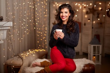 Young woman at fireplace with hot drink