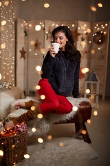 Young woman at home with hot drink in winter