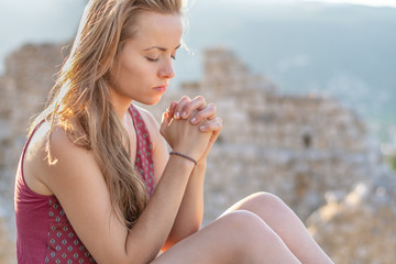 Christian worship and praise. A young woman is praying with ruins in the background.