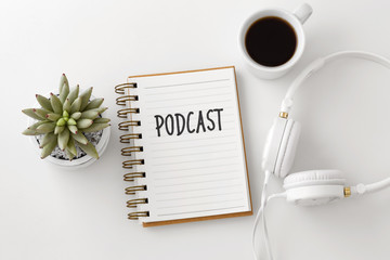 Podcast word on notebook with headphones