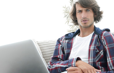 serious guy with laptop sitting on sofa