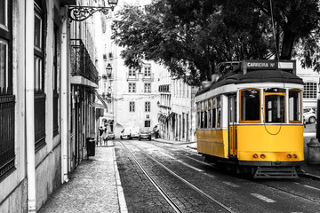 Yellow tram on old streets of Lisbon, Portugal, popular touristic attraction and destination. Black and white picture with a coloured tram.