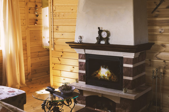 A cozy living room with a fireplace by the sofa and a forged table. Cozy winter concept. Christmas and travel