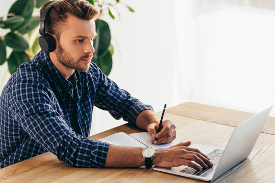 side view of man in headphones taking part in webinar at tabletop with notebook in office