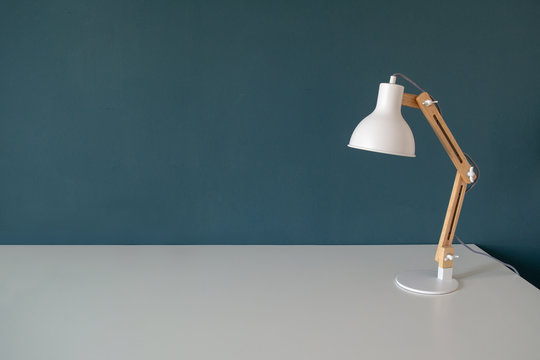 Office work desk with office lamp in a dark blue green background. White desk with copy space