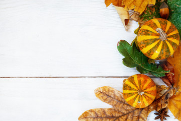 Autumn leaf with decorative pumpkins composition on old white vintage wooden texture floor. Fall, halloween concept. Flat lay, top view