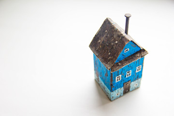Blue handmade wooden house model toy with metal roof and pin-chimney at white background