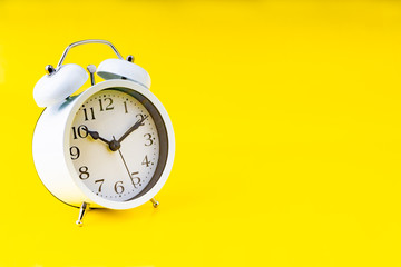 Clock on yellow background with selective focus and crop fragment. Copy space concept