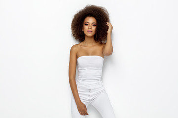 Wall Mural - Beautiful african american woman touching her afro isolated on white background