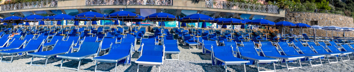 Panoramic view of blue chairs and parasol on the beach of Monterosso Al Mare village Italy