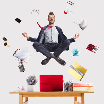 The young zen businessman relaxing at office in yoga pose lotus, while his work is doing. levitation concept