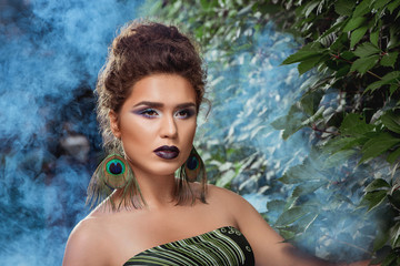Woman with make up posing against green bush in blue smoke.