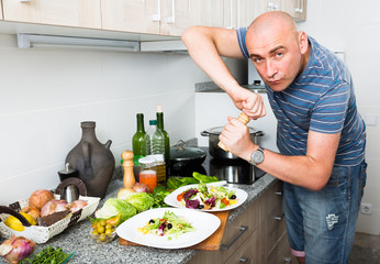 male prepares two salads and fills them with pepper