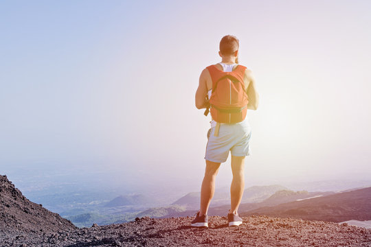 View of muscular young man standing behind climbed up the mountain and enjoy the beautiful views of nature. Concept hiking over rough terrain and health lifestyle, toned