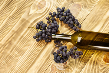 Image of a glass, freshly picked failed processing, black grapes on a wooden background and an empty bottle