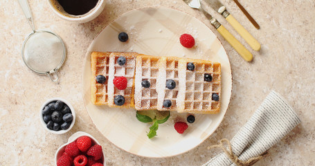 From above view of homemade waffles served on white plate decorated with ripe berries on beige background
