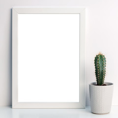 Photo of a white mockup frame against the background of an empty wall with a cactus with a gray flowerpot with a sweater pattern