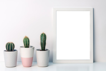 Photo of a white mockup frame on a background of empty copy space wall with cactuses of a gray pot with a pattern of sweater and one pink terrazzo