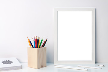 Photo of a white mockup frame with colored pencils in a wooden toolbox with notebooks on the desk