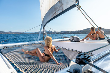 People tanning and relaxing on a summer sailin cruise, sitting on a luxury catamaran near picture perfect Palau town, Sardinia, Italy.