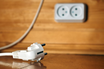 White electric plug lying on a floor with a socket on the wooden wall on the background