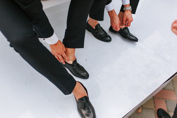 An elegant man puts on black, leather, formal shoes with plaster. Wedding problems