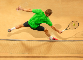 I am saving this ball now. Player lunge, game of defense. The one caucasian fit man playing tennis at the earthen court . Player jumping in full length with racquet and ball. Emotions on face. Upper