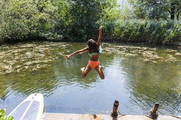 Carefree girl jumping into pond