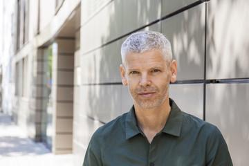 Portrait of a confident mature man at a building