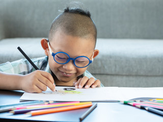 Boy intend drawing a picture fun, enjoy drawing or write in book at home.  .