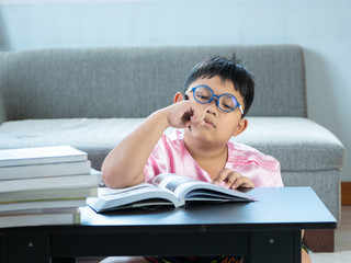 Asian boy tired and bored in write homework at home. education concept