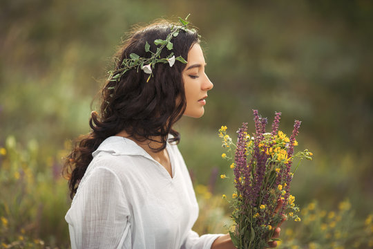 Beautiful young woman in white dress collecting wild flowers at the rural sunny landscape background in summer. Portrait of tender happy woman in wild field enjoying nature. Natural beauty model with