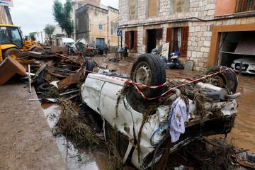Locals walk through debris as heavy rain and flash floods hit Sant Llorenc de Cardassar on the island of Mallorca