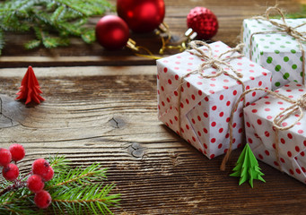 Gift wrapping. Christmas composition with present box, packing paper, festive decoration and fir tree branch. Preparation for holiday. Merry Christmas and Happy New Year concept.
