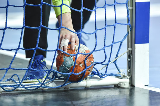 Hand of handball goalkeeper takes the ball from the goal.
